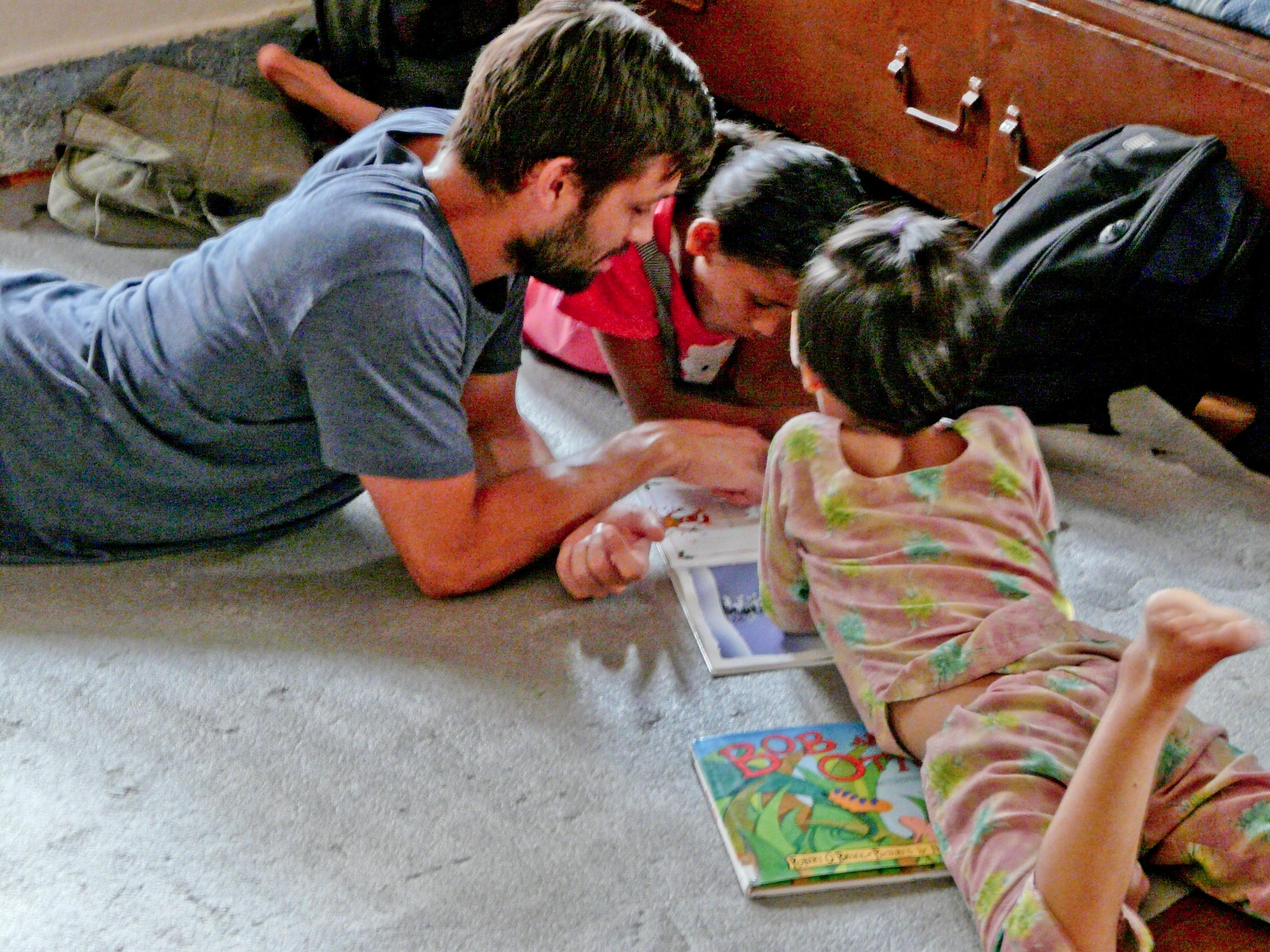 A Projects Abroad volunteer teaching English in Nepal reads a book to his students